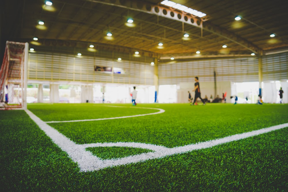 Corner Line of an indoor football soccer training field in Junior Soccer Academy school with blurred children and coach practicing on the background